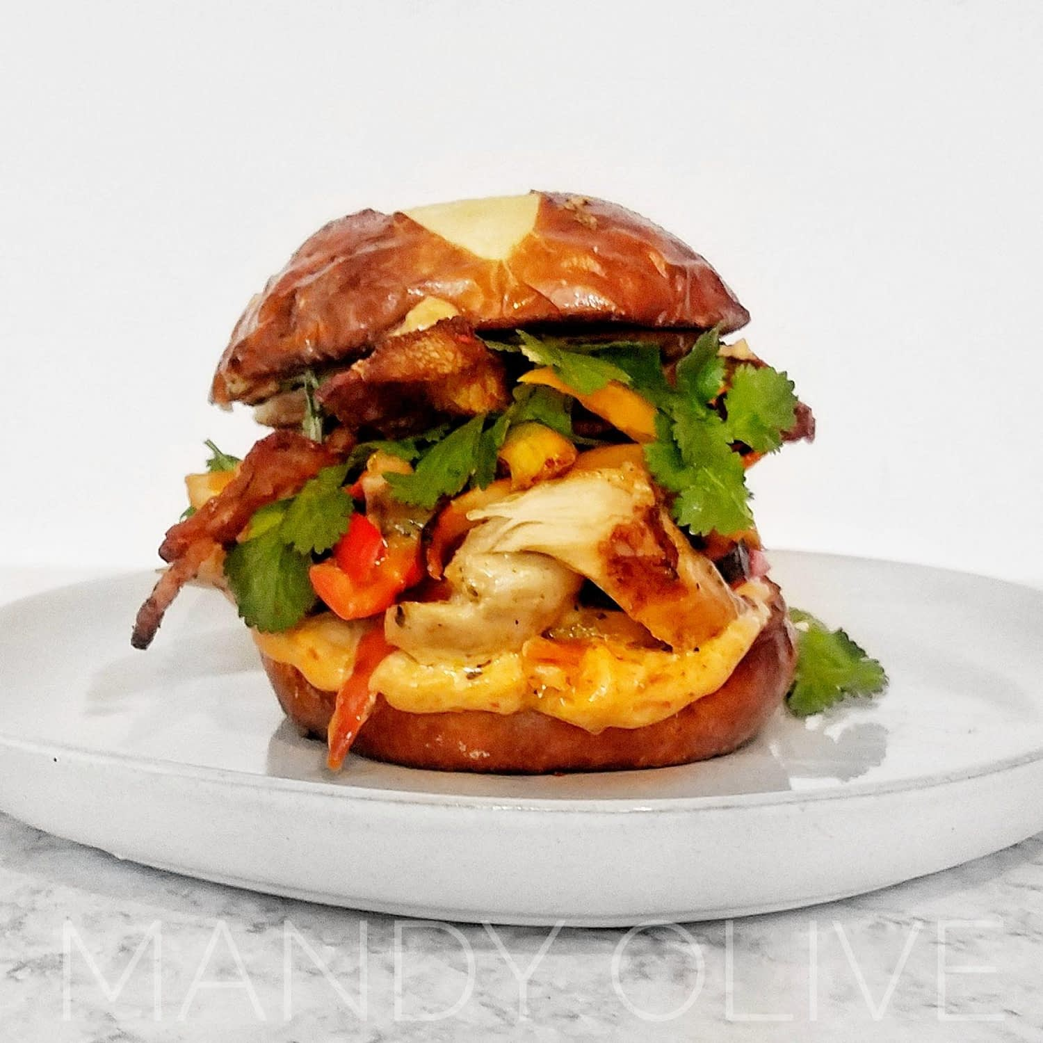 pulled chicken sandwich with chipotle mayo and bell peppers on a pretzel bun.