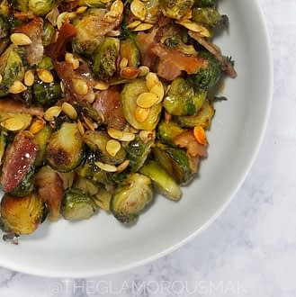 How to cook brussels sprouts in the oven. A healthy side dish with bacon and tahini maple dressing. This easy holiday recipe makes the best crispy caramelized brussels sprouts using fresh or frozen brussels sprouts, garlic and ginger. Bake it in the oven for a simple meal great for thanksgiving or christmas.