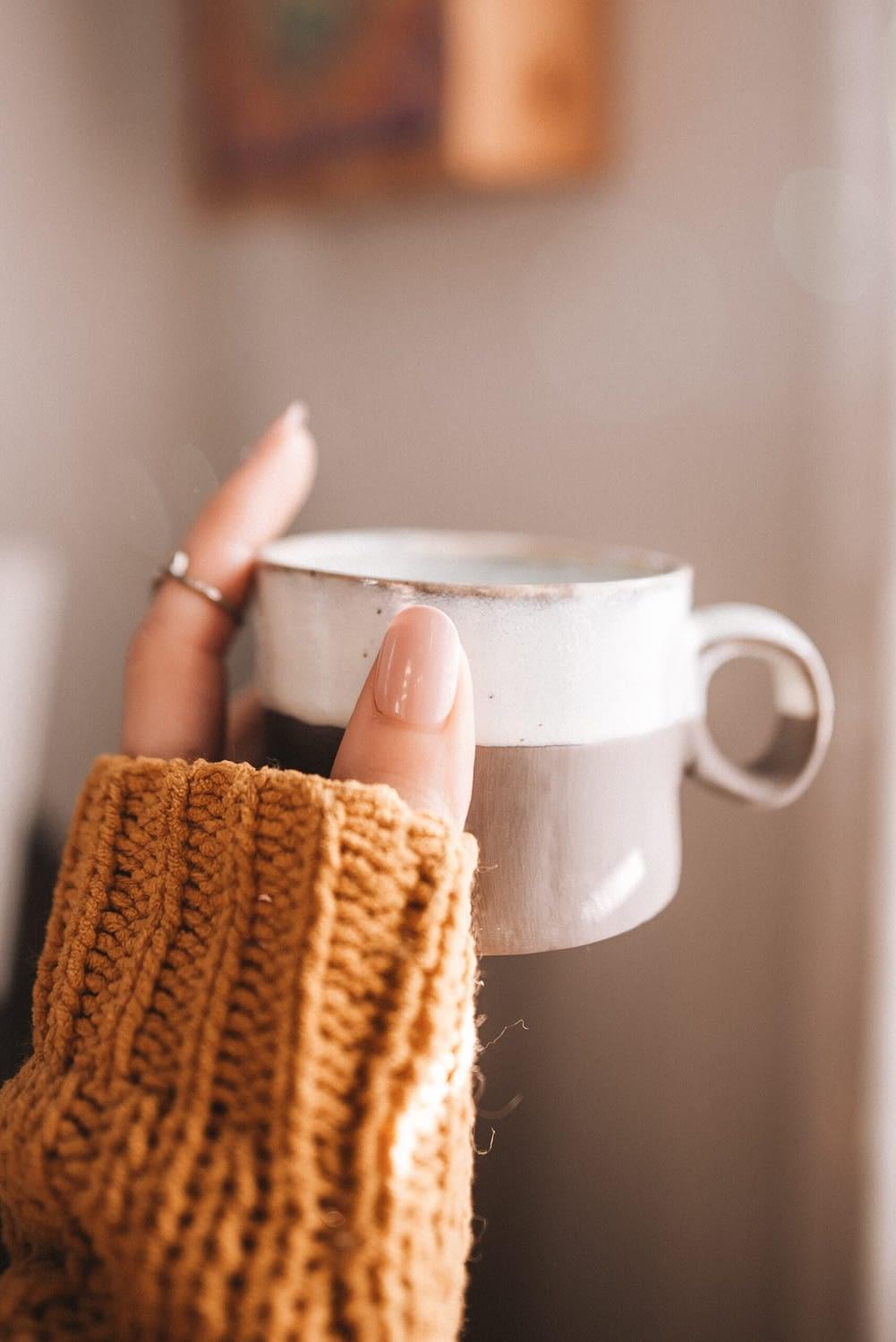 Starbucks copycat apple crisp macchiato recipe. woman with chunky sweater holding a white and grey mug.