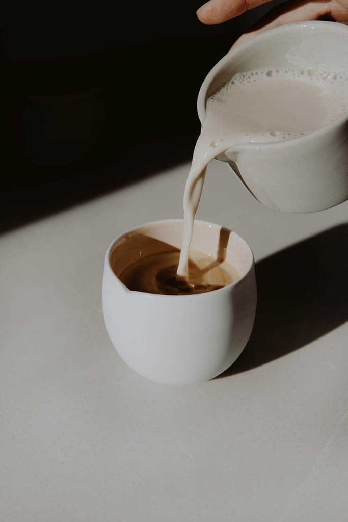starbucks apple crisp macchiato recipe. picture of milk being poured into white cup containing espresso.