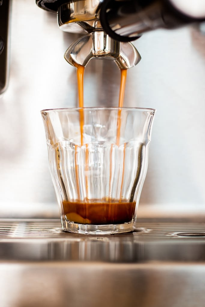 pulling espresso into a small glass depicted on post about espresso grind settings.