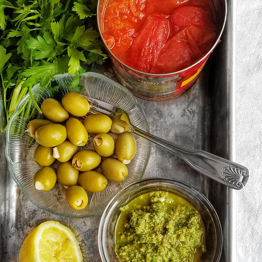 summer cooking tips: modern pantry must haves. garlic stuffed olives, tapenade and tomatoes pictured. Article found on mandyolive.com