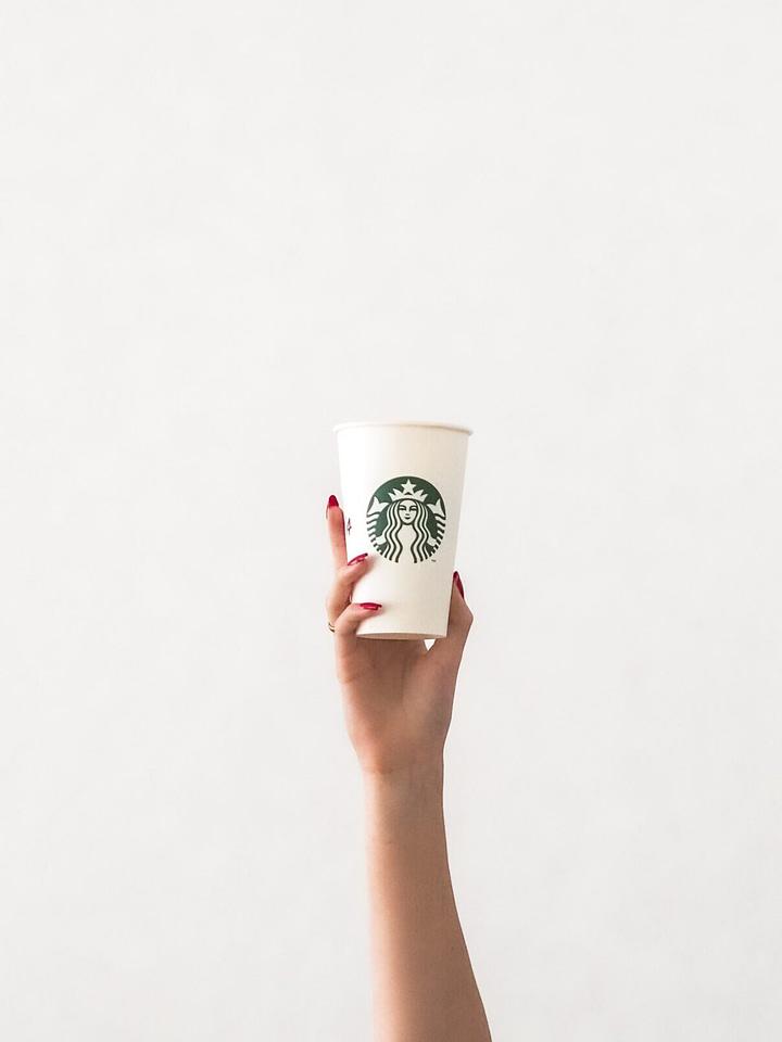 starbucks apple crisp macchiato copycat recipe. woman's arm holding starbucks cup against white bachground is pictured